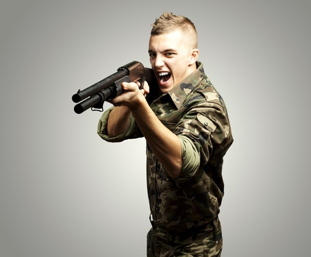 portrait of a young soldier aiming with shotgun over grey background photo