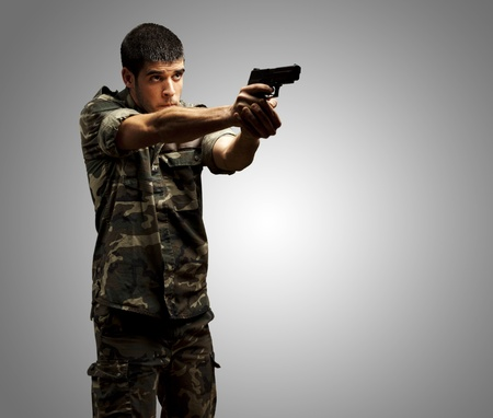soldier with rifle: portrait of a young soldier aiming with pistol against a grey background