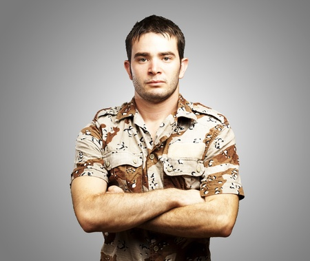 portrait of a serious young soldier standing against a grey background photo
