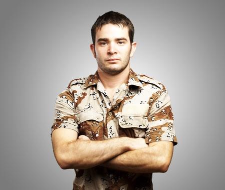 retrato de un joven soldado graves de pie contra un fondo gris Foto de archivo