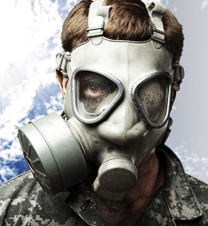 portrait of young soldier wearing gas mask against a cloudy sky background photo