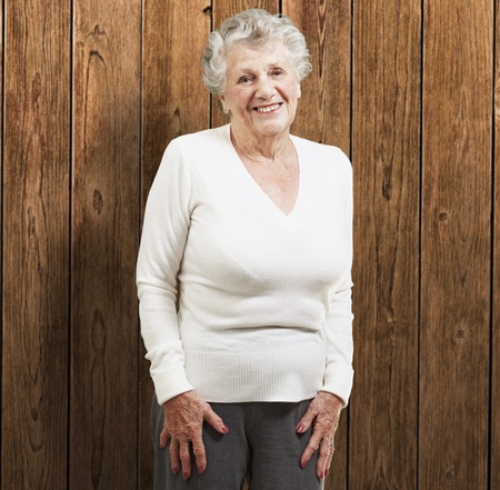 pretty senior woman smiling against a wooden background photo