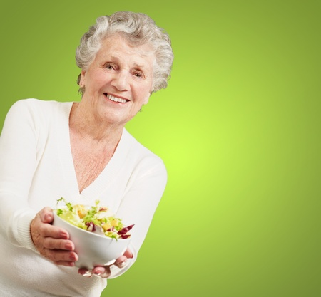 old people eating: portrait of senior woman showing a fresh salad over green background Stock Photo