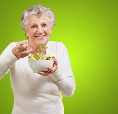 portrait of senior woman eating a fresh salad over green background Stock Photo - 12656497