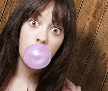 young woman with a pink bubble gum against a wooden background photo