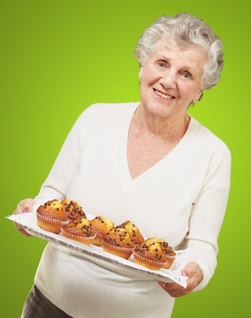 portrait of senior woman showing homemade muffins over green Stock Photo - 12656453