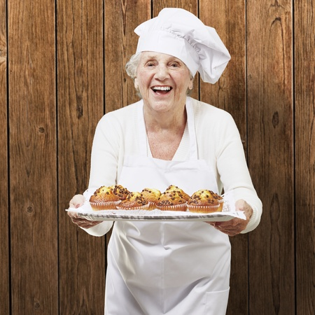 senior woman cook holding a tray with muffins against a wooden background photo