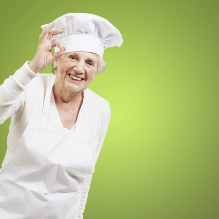 senior woman cook doing an excellent symbol against a green background photo
