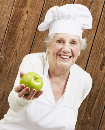 senior woman cook offering a green apple against a wooden background photo