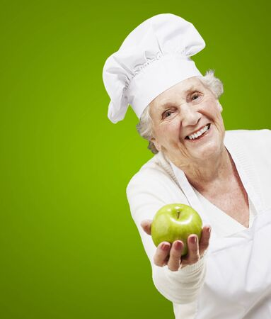 senior woman cook offering a green apple against a green background photo