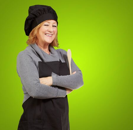 portrait of woman cook wearing apron over green background photo