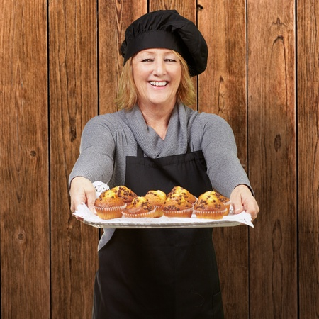 portrait of cook woman showing a homemade muffins tray against a wooden wall Stock Photo - 12656477