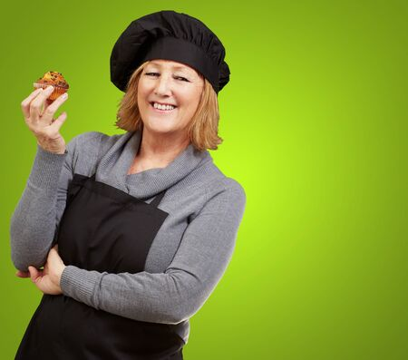 portrait of middle aged cook woman holding a delicious homemade muffin over green background photo