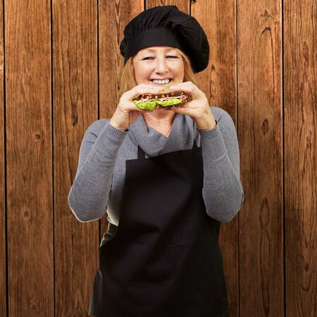 vegetal: Middle aged cook woman holding a vegetal sandwich against a wooden wall