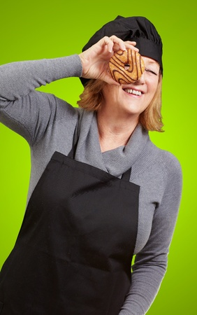 Middle aged cook woman looking through a donut over green background photo