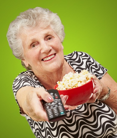 portrait of senior woman holding pop corn bowl and changing channel of tv over green background photo