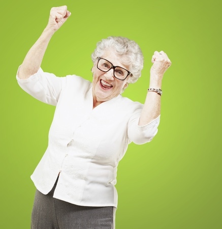 portrait of a cheerful senior woman gesturing victory over green background photo