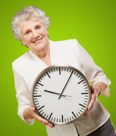 portrait of a happy senior woman holding clock over green photo