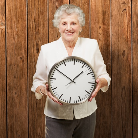 portrait of a happy senior woman holding clock against a wooden background photo