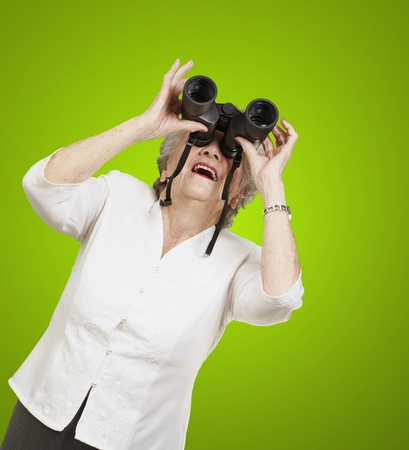 portrait of senior woman looking through a binoculars against a green background photo