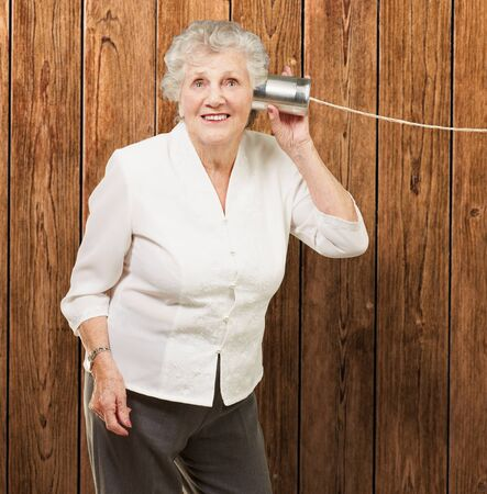 tin can telephone: portrait of senior woman hearing with metal tin can against a wooden wall