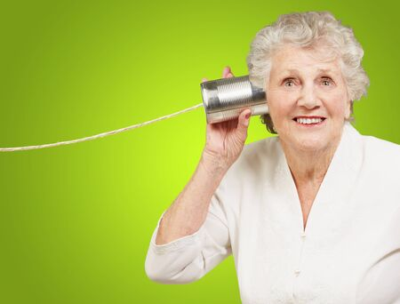 cans: portrait of senior woman hearing with metal tin can over green background Stock Photo