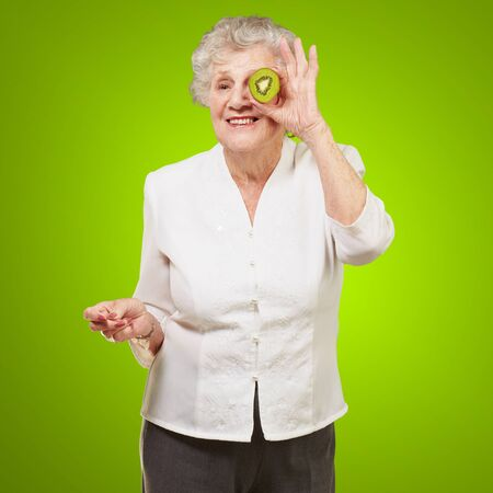 portrait of senior woman holding kiwi in front of her eye over green background photo