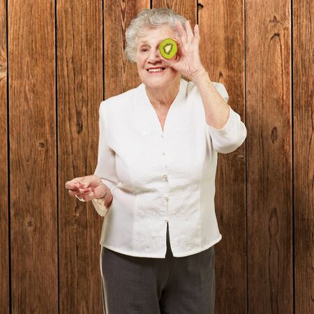 portrait of senior woman holding kiwi in front of her eye against a wooden wall Stock Photo - 12656518