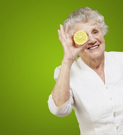 portrait of senior woman with lemon in front of her eye over green photo