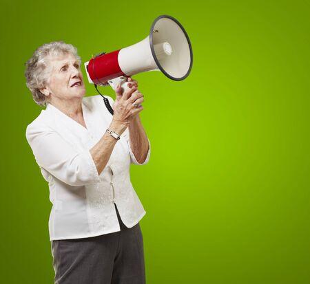 portrait of senior woman holding megaphone over green background Stock Photo - 12656395