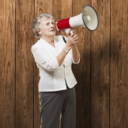 portrait of senior woman holding megaphone over wooden wall Stock Photo - 12656495
