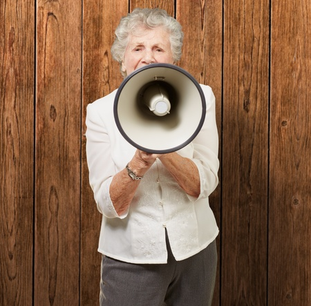 portrait of senior woman screaming with megaphone against a wooden wall photo