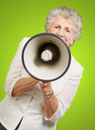 portrait of senior woman screaming with megaphone over green background photo