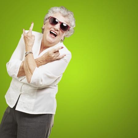 portrait of senior woman doing rock symbol over green background photo