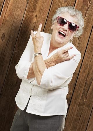 portret van senior vrouw doet rots symbool tegen een houten wand