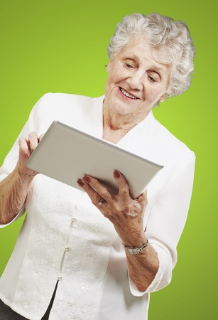 portrait of senior woman touching digital tablet over green background photo