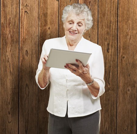 portrait of senior woman touching digital tablet against a wooden wall photo