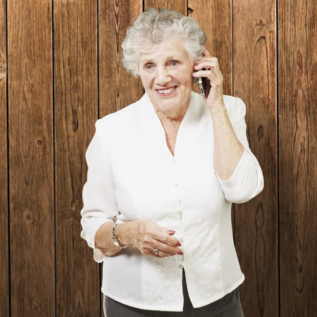 portrait of senior woman talking on mobile against a wooden wall photo