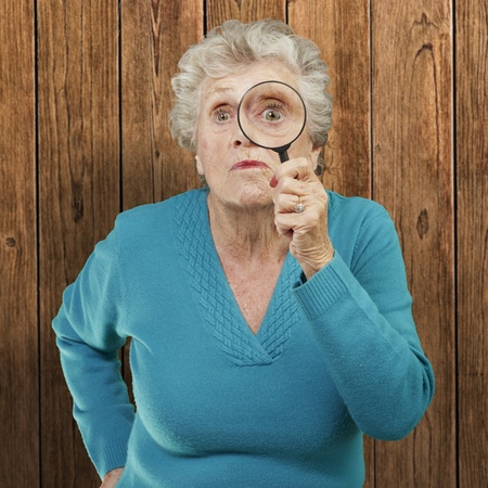 portrait of senior woman looking through a magnifying glass against a wooden wall Stock Photo - 12656473