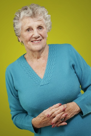 portrait of senior woman standing over yellow background photo