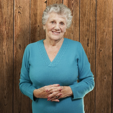 portrait of senior woman standing against a wooden wall photo