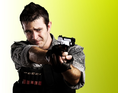 special agent: portrait of young soldier pointing with a gun against a yellow background
