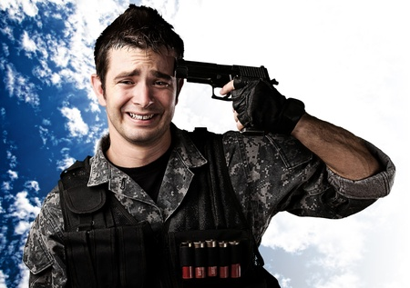 portrait of young soldier committing suicide against a cloudy sky background photo