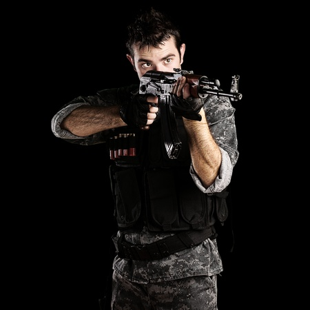 assault forces: portrait of young soldier pointing with rifle against a black background