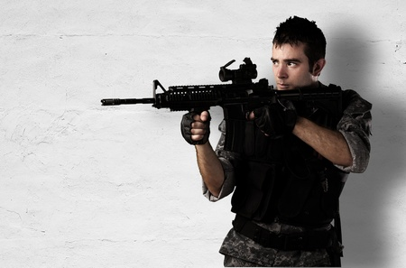 young soldier pointing with rifle against a white wall photo