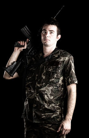 man holding gun: young soldier holding a rifle on a black background Stock Photo