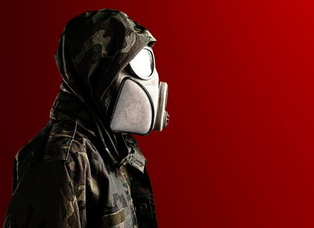 vintage military rifle: portrait of soldier with gas mask against a red background
