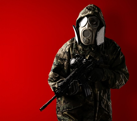 portrait of soldier with mask and rifle against a red background photo