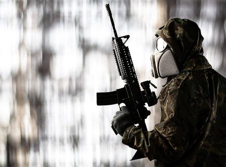 mascara de gas: retrato de la máscara de gas soldado de vestir y apuntando con la escopeta contra el fondo abstracto