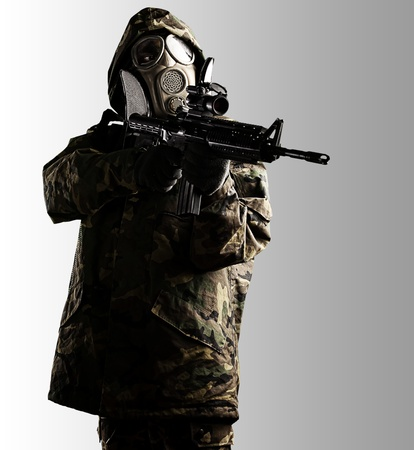 soldier with camouflage coat, rifle and gas mask over grey photo
